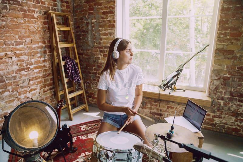 De muziek van de vrouwenopname, het spelen trommels en thuis het zingen royalty-vrije stock fotografie