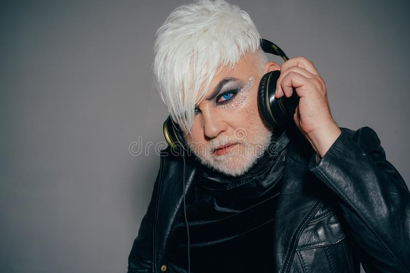 De muziek is wat ik ben Gebaarde mens met de mannelijke hoofdtelefoons van de make-upslijtage De transsexueelpersoon luistert aan royalty-vrije stock fotografie