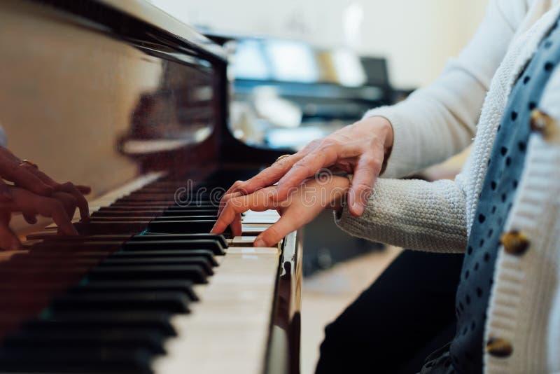 De muziekleraar helpt student correct te spelen stock afbeelding