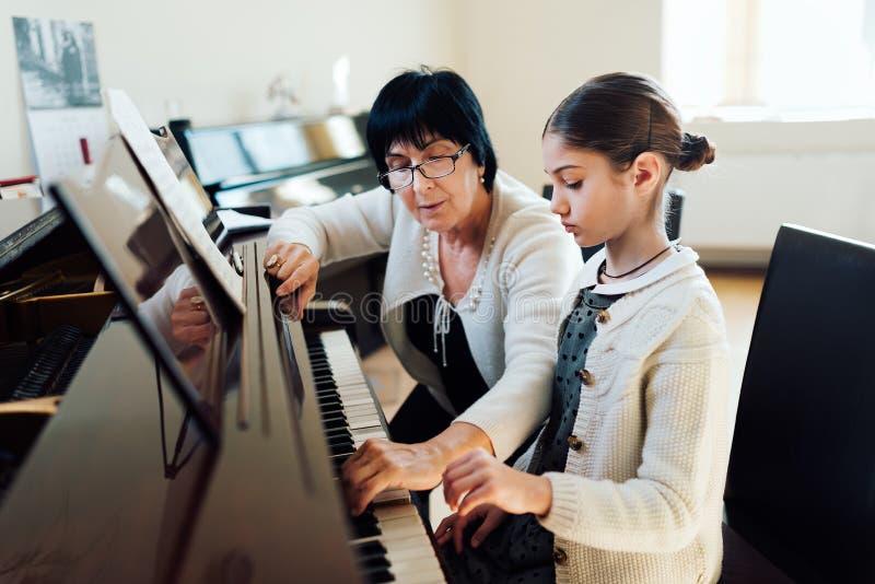 De muziekleraar toont hoe te om piano te spelen stock fotografie