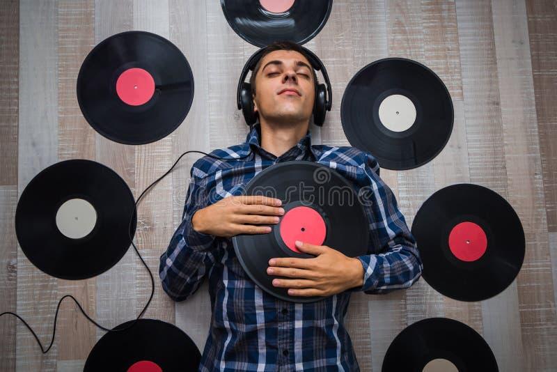 De muziekminnaar met hoofdtelefoons ligt op de vloer en luistert muziek stock afbeeldingen