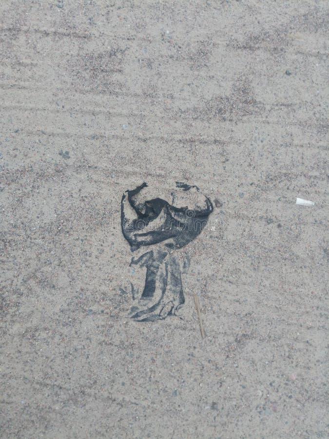 De mystieke zwarte mantel voert rituele handelingen uit Een stuk van vod op het zand Foto met exemplaarruimte royalty-vrije stock fotografie