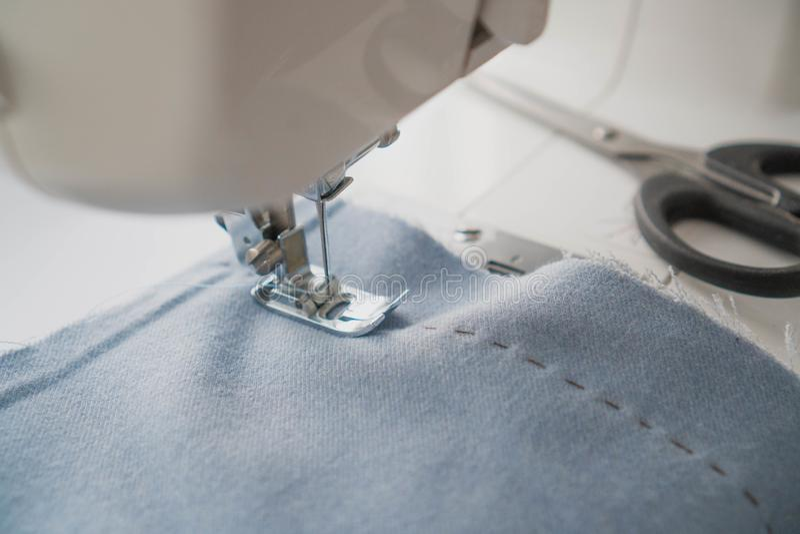 De naaimachine presser voet drukt de blauwe stof Naaimachine en punt van blauwe kleding De schaar is dichtbij blauwe stof royalty-vrije stock afbeeldingen