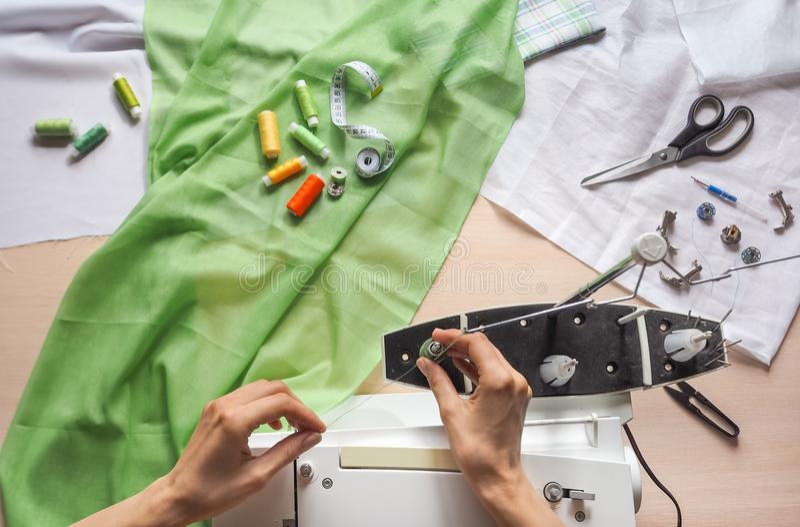 De naaisterswerken aangaande een naaimachine Stadia van de productiecyclus op een naaimachine royalty-vrije stock afbeeldingen