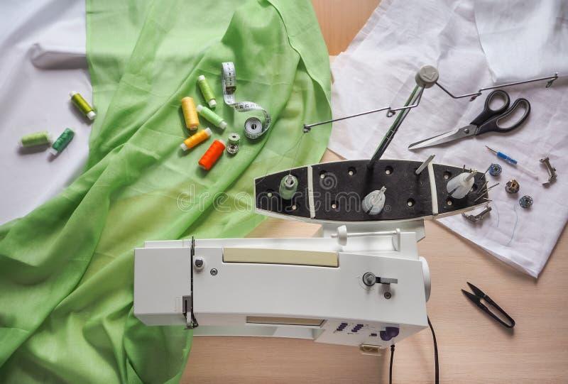 De naaisterswerken aangaande een naaimachine Stadia van de productiecyclus op een naaimachine stock afbeeldingen