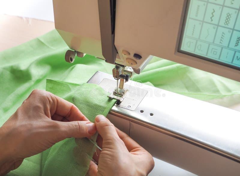 De naaisterswerken aangaande een naaimachine Stadia van de productiecyclus op een naaimachine stock foto