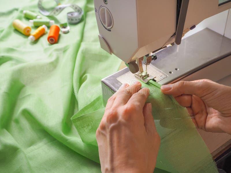 De naaisterswerken aangaande een naaimachine Stadia van de productiecyclus op een naaimachine royalty-vrije stock afbeelding