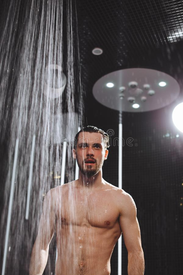 De naakte brutale kerel gaat een douche nemen koel neer in douche koel hoofd royalty-vrije stock afbeelding