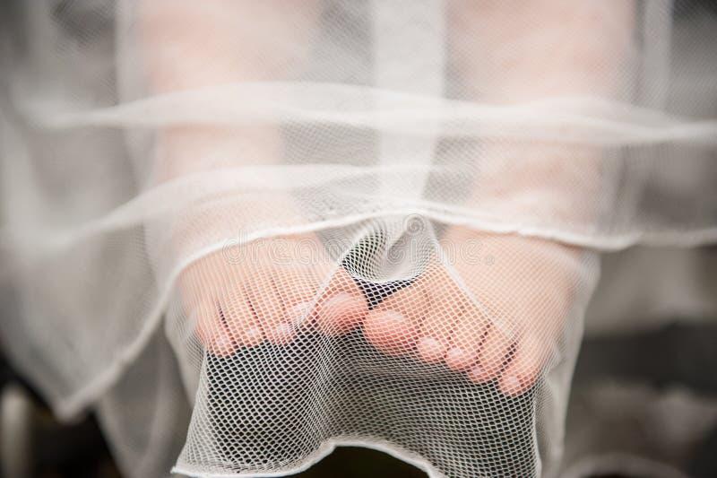 De naakte voeten van close-upkinderen ` s onder het gordijn Babyjongen op huwelijk Weinig babytenen onder de doek stock afbeeldingen