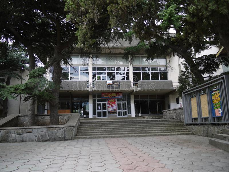 De naaldbomen boven de ingang aan twee-storeyed huis van cultuur met affiches, treden en een platform voor stock afbeelding