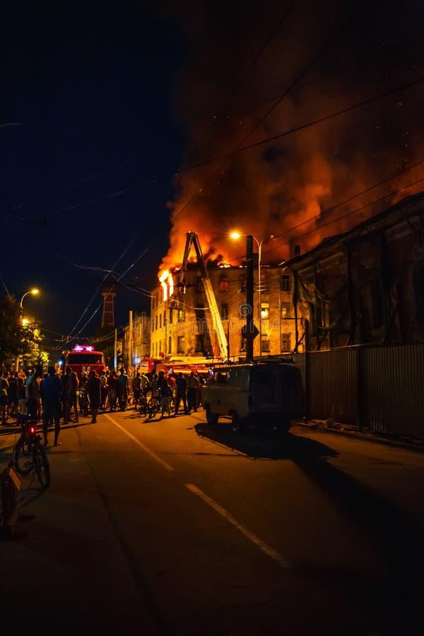 De nachtbrand in flatgebouw, brandbestrijders worstelt met rond vlam, silhouetten van onherkenbare mensentribune stock foto