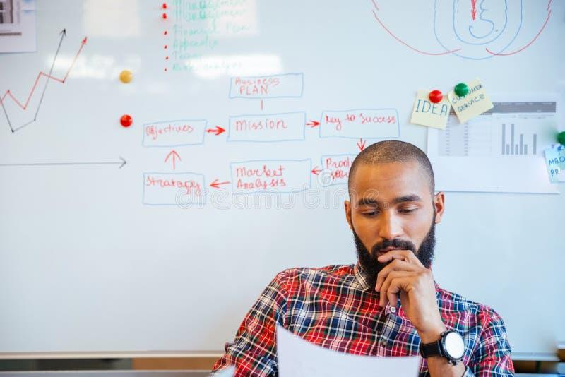 De nadenkende Afrikaanse Amerikaanse zitting van de mensenlezing over whiteboard stock afbeeldingen