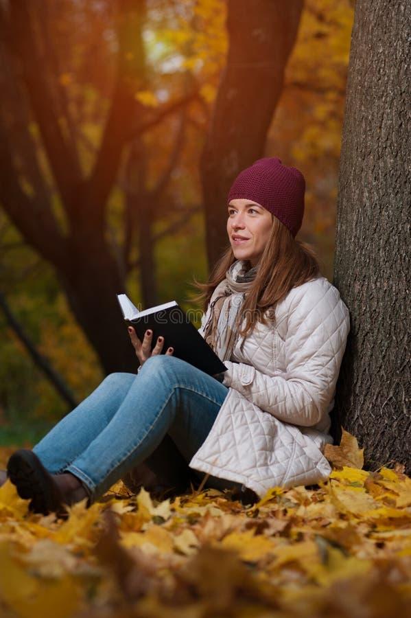 De nadenkende jonge vrouwelijke studentenzitting parkeert in de herfst royalty-vrije stock foto