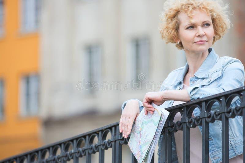 De nadenkende kaart op middelbare leeftijd van de vrouwenholding terwijl het leunen op traliewerk stock foto