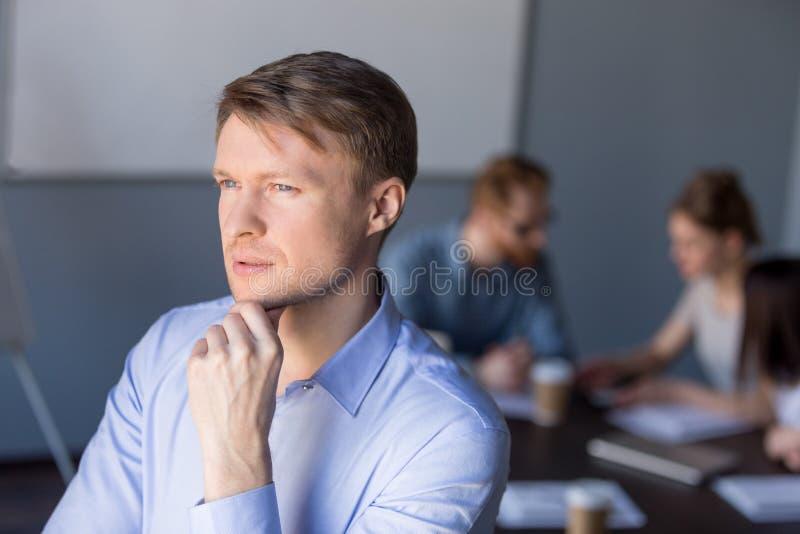 De nadenkende mannelijke werknemer kijkt in afstand denkend over succes stock afbeeldingen