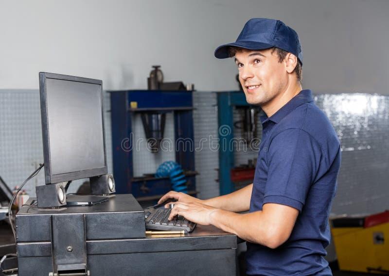 De nadenkende Mechanische Reparatiewerkplaats van Using Computer In royalty-vrije stock afbeelding