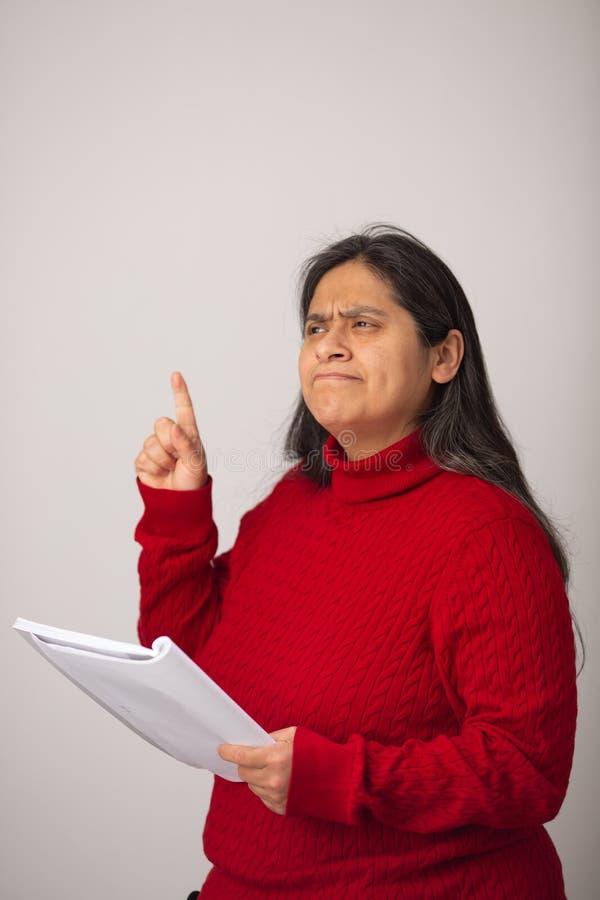 De nadenkende Spaanse Vrouw houdt Notitieboekje terwijl het Benadrukken van Vinger stock afbeelding