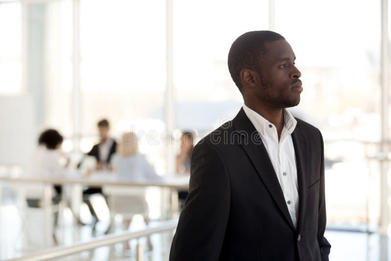 De nadenkende zwarte werknemer kijkt in afstand dromend van succes royalty-vrije stock foto