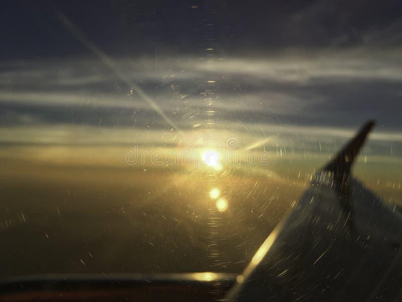 De nadruk van het vliegtuigvenster met zon op de hemel die van de horizonwolk door wordt geplaatst stock fotografie