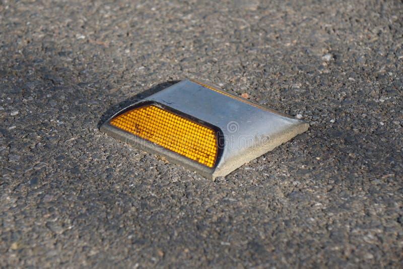 De nagel van de metaalweg met gele reflector op asfaltweg in Thailand stock afbeeldingen
