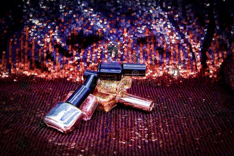 De nagellakken met metaal schittert, flessen kleurrijk voor manicure op de zwarte achtergrond van discolichten royalty-vrije stock foto's