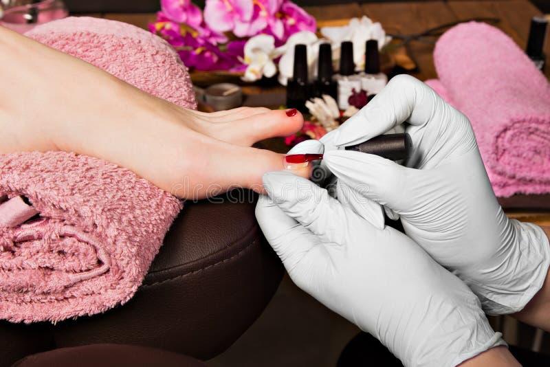 De nagelverzorging van de close-upvinger door pedicurespecialist in schoonheidssalon stock afbeeldingen