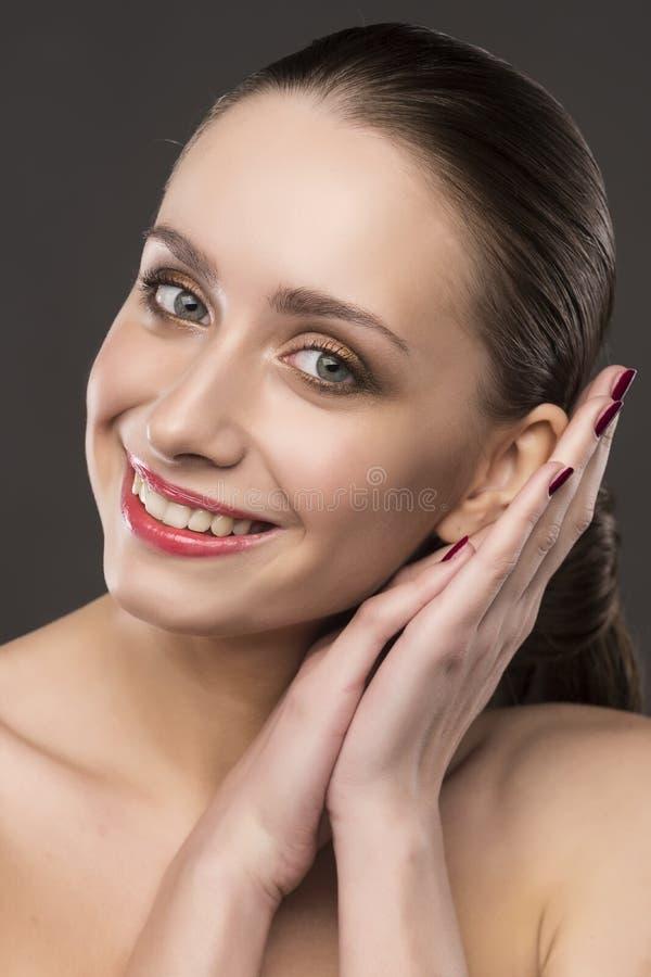 De nakna skuldrorna för den härliga flickan ler på en grå bakgrund arkivbilder