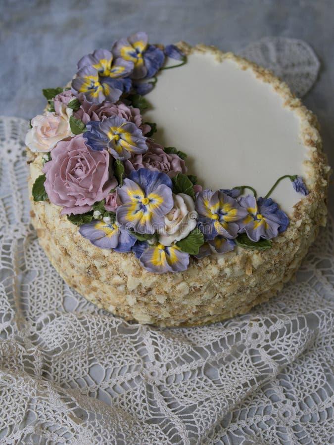 De Napoleoncake met vanilleroom, met buttercream wordt verfraaid bloeit - rozen die en pansies Uitstekende stijl Grijze achtergro royalty-vrije stock afbeelding