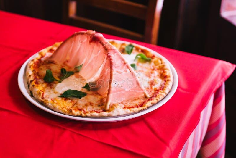De Napolitaanse Pizza maakte met tomaten en mozarellakaas en bovenste laagje met de hambrug van Parma op rood tafelkleed met stoe stock foto