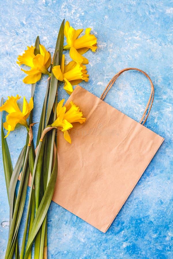 De narcissenbloemen zijn geel op een blauwe marmeren achtergrond en ambachtdocument zak, is er een lege ruimte voor tekst Vlak le stock foto