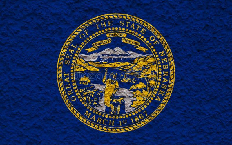 De nationale vlag van de V.S. verklaart binnen Nebraska tegen een grijze muur met steenachtige oppervlakte op de dag van onafhank stock foto
