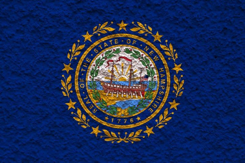 De nationale vlag van de V.S. verklaart binnen New Hampshire tegen een grijze muur met steenachtige oppervlakte op de dag van ona stock afbeelding