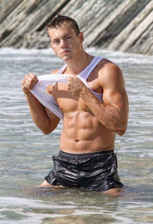 De natte sexy mens van de spier in overzees water royalty-vrije stock foto's