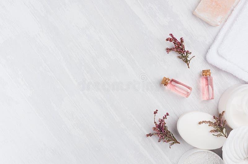 De Natural spa schoonheidsmiddelen met roze roze olie, zout, zeep en lavendel bloeit op witte houten achtergrond, hoogste mening, stock foto