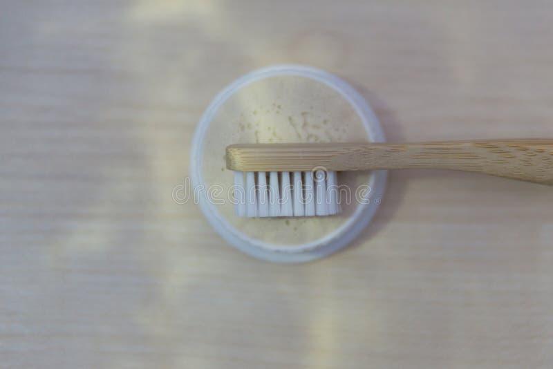 De natuurlijke bamboetandenborstel met houten handvat en wit varkenshaar ligt op een ronde doos met natuurlijke tandpasta en een  royalty-vrije stock afbeelding