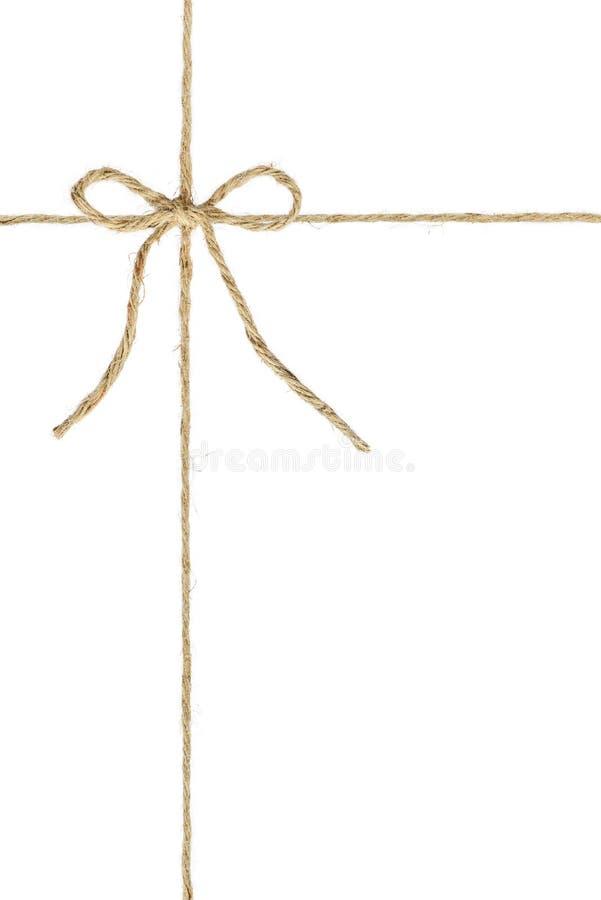 De natuurlijke bruine de hennepkabel van de jutestreng, bindt een knoop/een boog in het midden van het koord stock fotografie