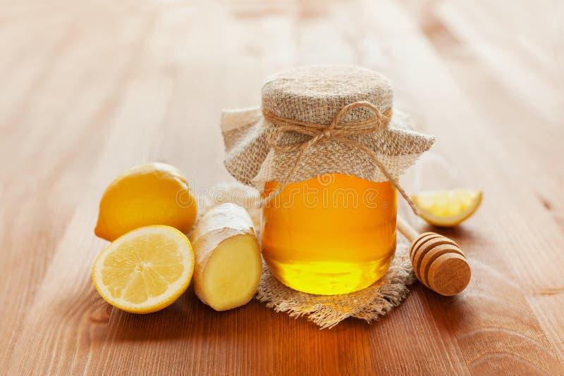 De natuurlijke honing in een pot of de kruik met streng bond een boog vast stock afbeeldingen