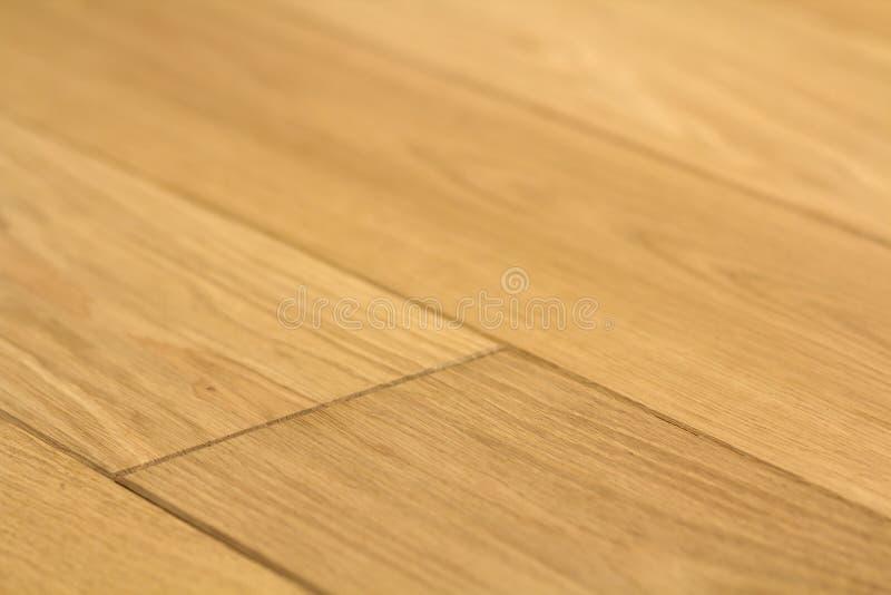 De natuurlijke lichtbruine houten raad van de parketvloer Zonnige zachte gele textuur, achtergrond van het exemplaar de ruimteper stock afbeelding