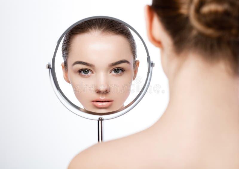 De natuurlijke make-up die van het schoonheidsmeisje in spiegel kijken stock foto