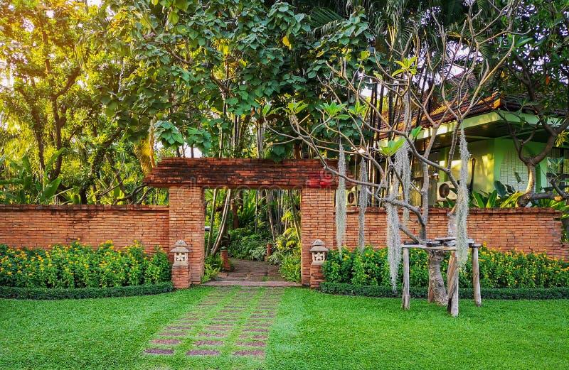 De natuurlijke oranje kleibaksteen overspande muuringang in een tropische tuin met patroon van bruine laterite gang op groen gras royalty-vrije stock fotografie