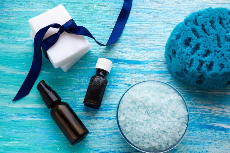 De natuurlijke organische etherische olie van zeepflessen en overzees zout kruidenbad op een blauwe houten lijst stock foto's