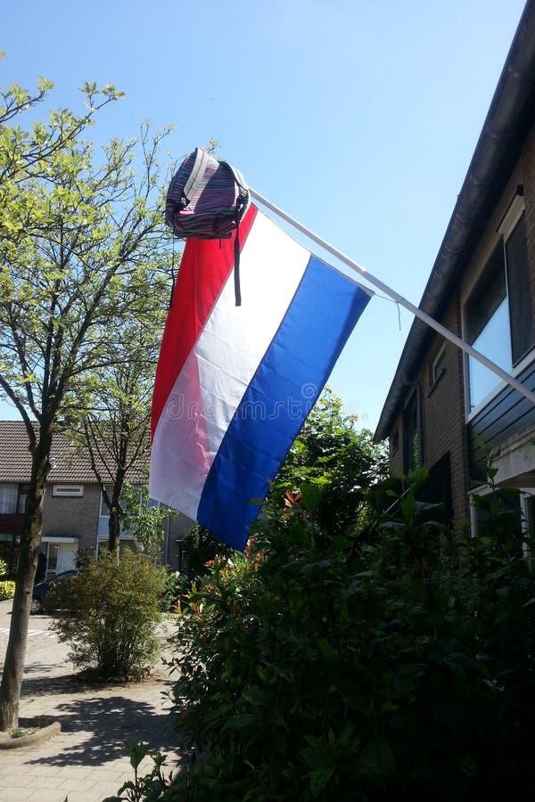 De Nederlandse vlag hangt uit met schooltas om dat één van de jonge geitjes te vieren is overgegaan t stock fotografie