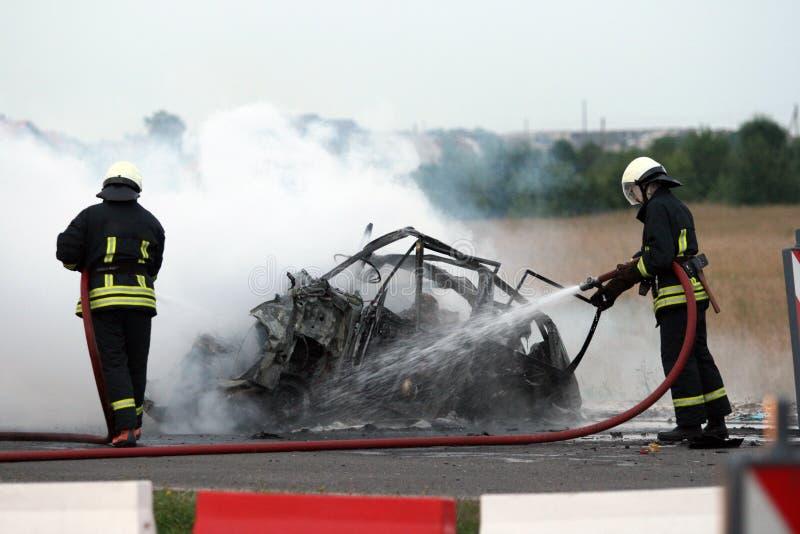 De neerstorting op een autosnelwegbrandbestrijders dooft een brandende auto stock afbeeldingen