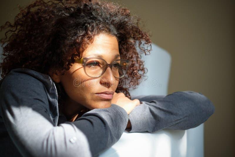 De negatieve emoties die van het vrouwengevoel op de bank liggen stock foto's