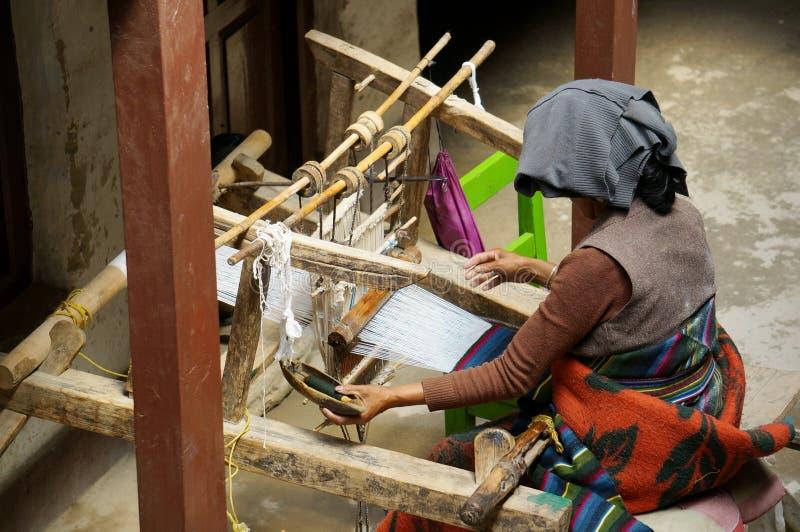 De Nepalese vrouw vlecht manueel de mat op een oud eigengemaakt weefgetouw, in de stad van Lo Mantang stock foto's