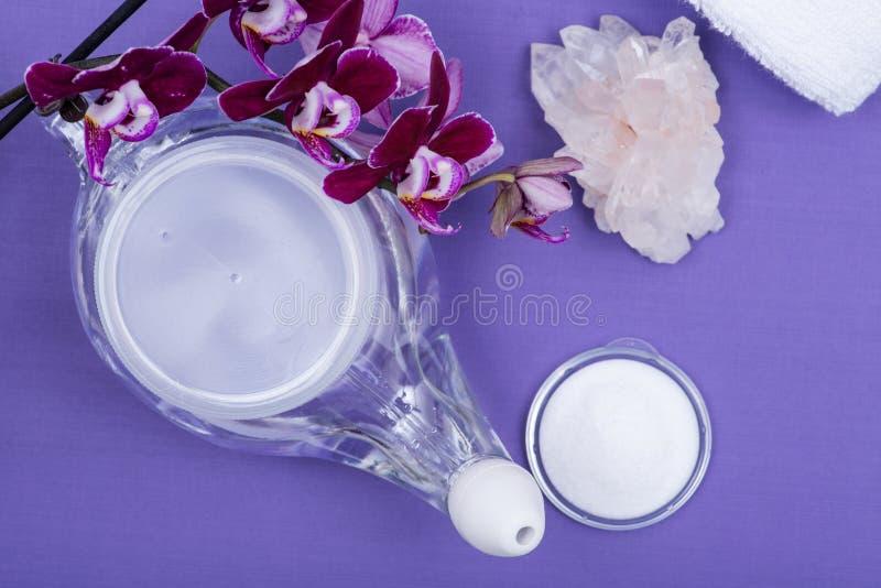 De Netipot, stapel van Zoute, Purpere Orchidee bloeit, Duidelijke Kwartscluster en opgerolde Witte Handdoeken op purpere achtergr royalty-vrije stock foto's