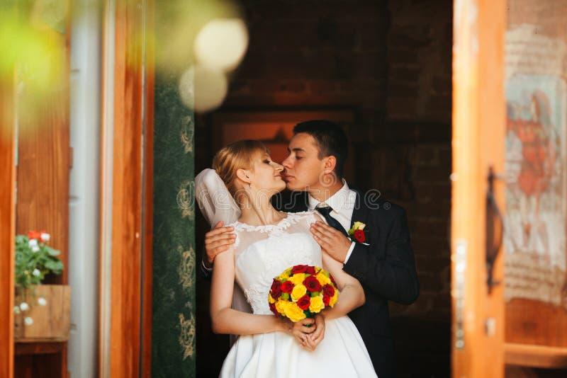 De neus die van de bruid van bruidegomaanrakingen teder haar houden van erachter in a royalty-vrije stock afbeelding