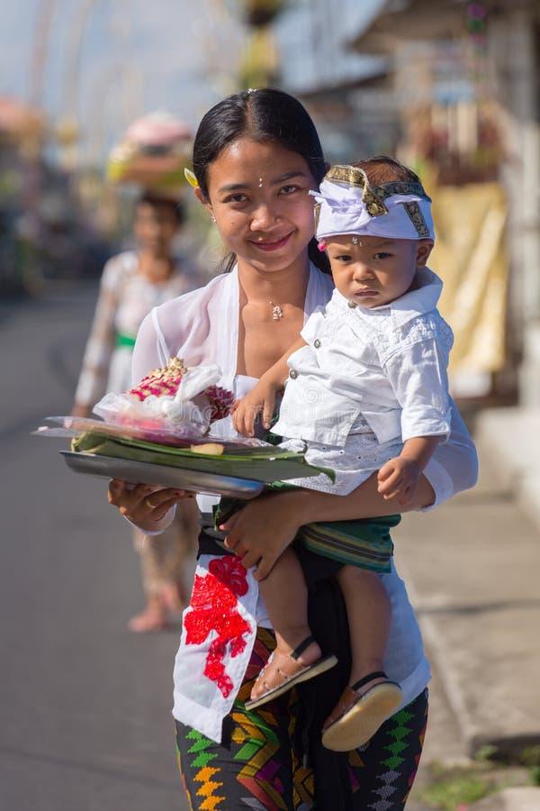 De niet geïdentificeerde Balinese vrouw met een kind draagt dienstenaanbod voor goden tijdens Galungan en Kuningan in Ubud, Bali royalty-vrije stock afbeeldingen