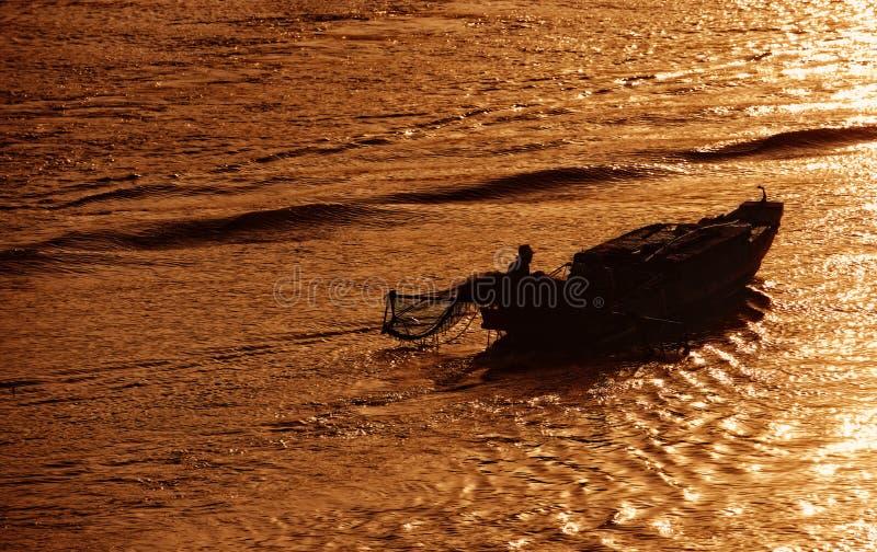 De niet geïdentificeerde controle die van de vissersmens met oude boot in vroege ochtend gaan van rivier in Ben Tre, Vietnam stock foto