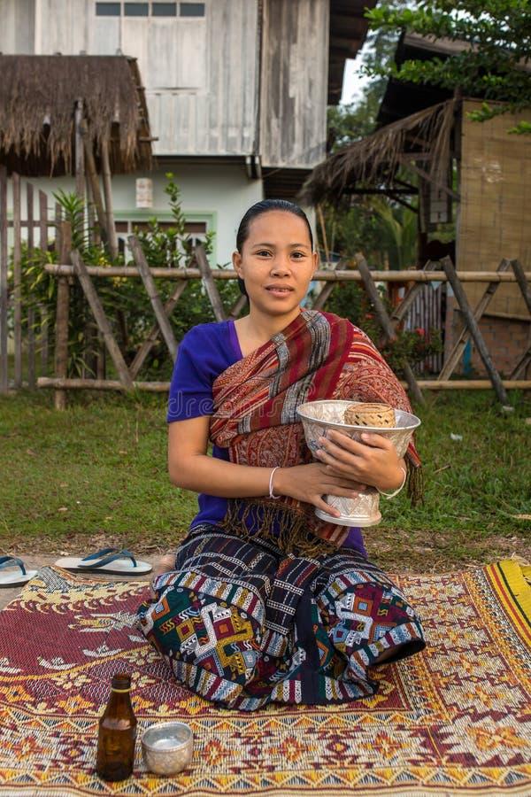 De niet geïdentificeerde lao vrouw wacht op Boeddhistenmonniken om hen aalmoes te geven stock afbeeldingen